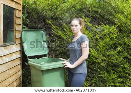 Portrait of young woman near conteiner for garden waste
