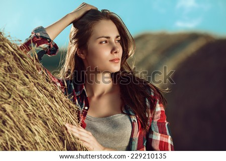 Portrait of young woman next to a stack of hay in sunlight - stock photo