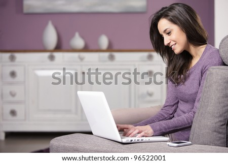 portrait of young woman on the sofa using laptop - stock photo