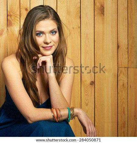 Portrait of young woman on wood background. Beautiful female model posing. Long hair.