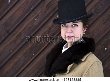 Portrait of young woman on wooden wall background