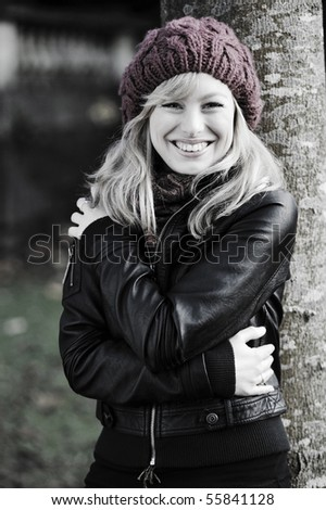 Portrait of young woman outdoors, leaning against a tree - stock photo