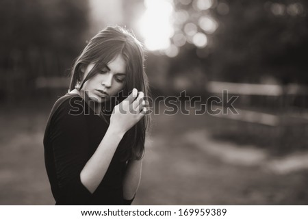 Portrait of young woman outside in black and white. Caucasian woman with long hair  on sunny summer day. - stock photo