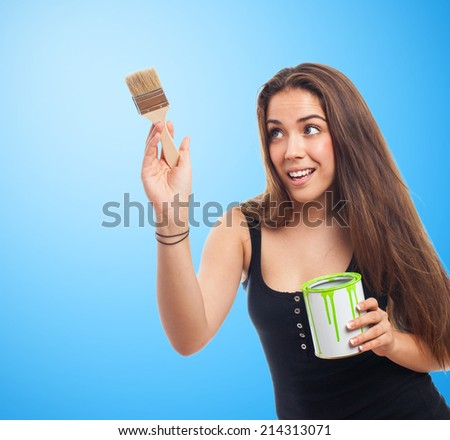 portrait of young woman painting and holding a paint can - stock photo