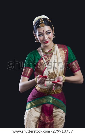 Portrait of young woman performing Indian classical dance over black background - stock photo