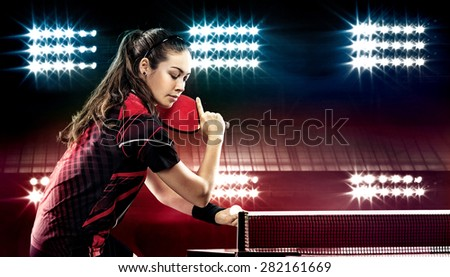 Portrait Of Young Woman Playing Tennis On Black Background with lights - stock photo