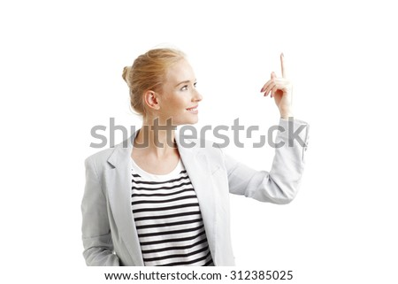 Portrait of young woman points out something while standing at isolated on white background.