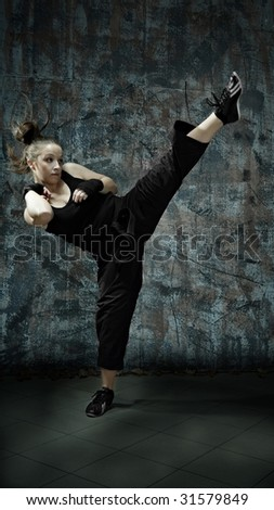 Portrait of young woman practice martial arts - high kick - stock photo