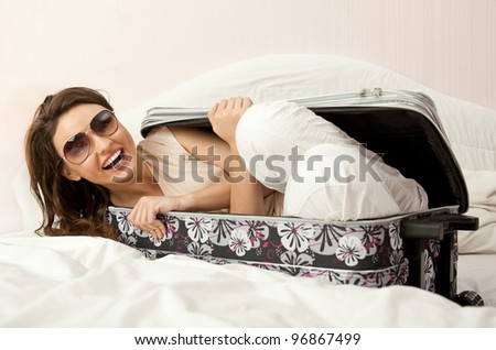 Portrait of young woman preparing for a trip and hiding inside her suitcase - stock photo