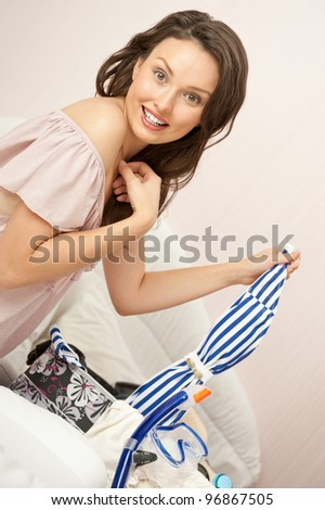 Portrait of young woman preparing for big trip and vacation she can not wait and have a big fun with packing her props and clothes - stock photo