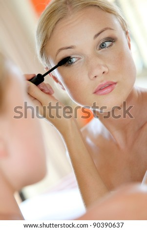 Portrait of young woman putting mascara on - stock photo