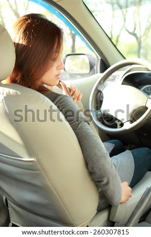 portrait of young woman putting on safety belt in the car