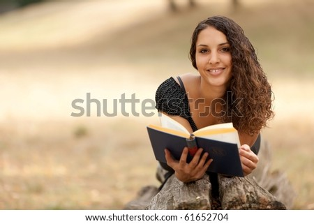 portrait of young woman reading book lying on tree trunk