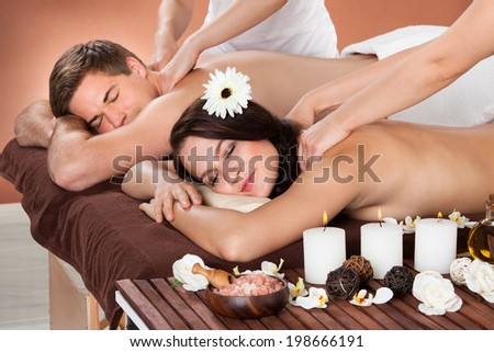 Portrait of young woman receiving shoulder massage with man in background at spa - stock photo