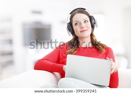 Portrait of young woman relaxing at home while using laptop and listening music.  - stock photo