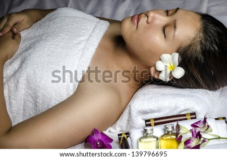 Portrait of young woman relaxing at spa and massage - stock photo