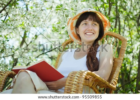 portrait of young woman relaxing in   blossoming garden