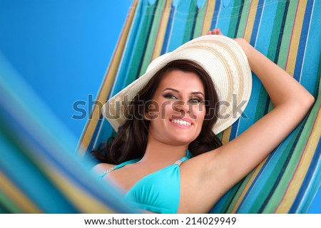 Portrait of young woman relaxing in hammock - stock photo