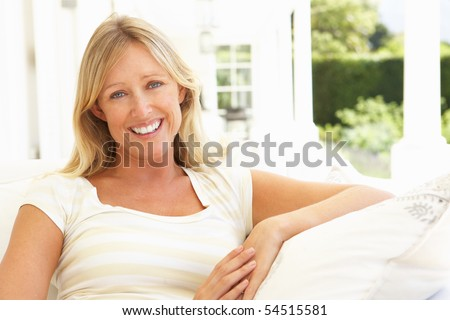 Portrait Of Young Woman Relaxing On Sofa - stock photo