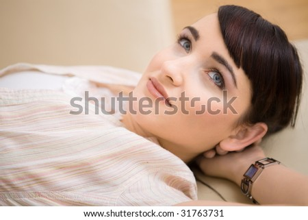 Portrait of young woman resting on a couch at home, smiling.
