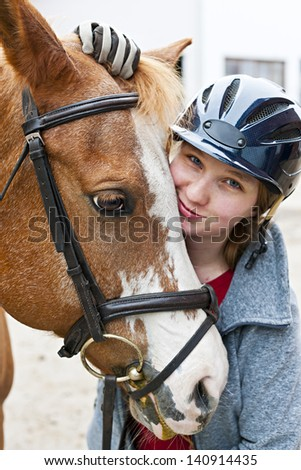 Portrait of young woman rider with brown horse - stock photo
