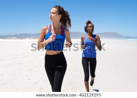 Portrait of young woman running with her friend in the background on the beach
