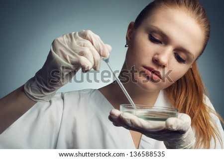 Portrait of young woman - scientist with dropper working at the laboratory. Studio shot - stock photo