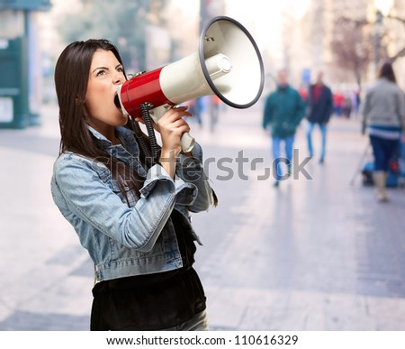 portrait of young woman screaming with megaphone at crowded street - stock photo