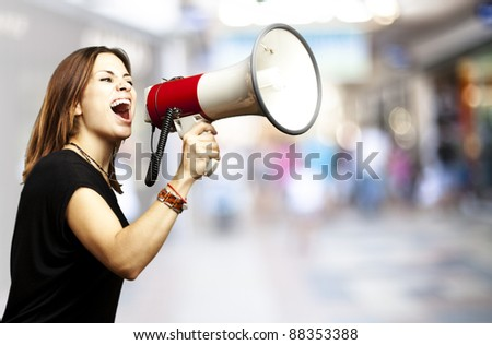 portrait of young woman shouting using megaphone against a crowded place - stock photo