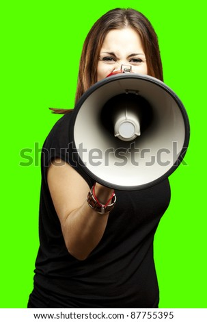 portrait of young woman shouting with megaphone against a removable chroma key background