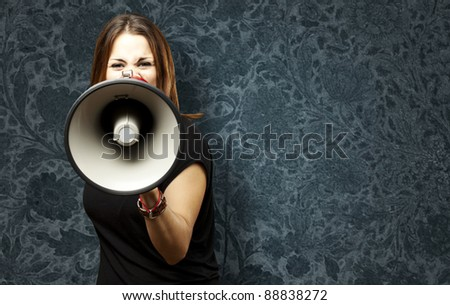 portrait of young woman shouting with megaphone against a vintage wall - stock photo