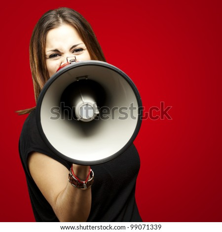 portrait of young woman shouting with megaphone over red