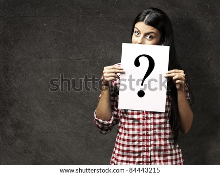 portrait of young woman showing a interrogation symbol against a grunge background - stock photo