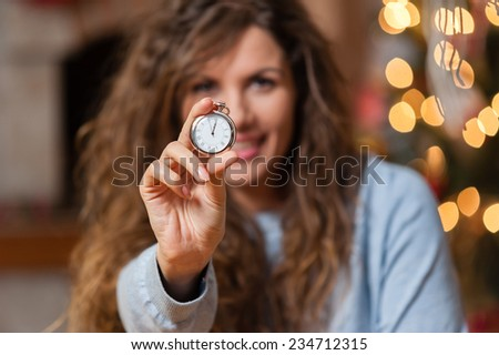 Portrait of young woman showing pocket watch in front of christmas tree over living room - stock photo