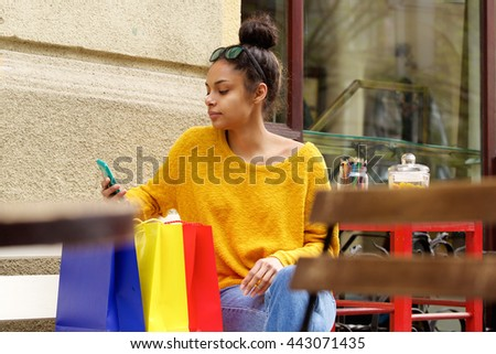 Portrait of young woman sitting at outdoor cafe with shopping bags looking at her mobile phone