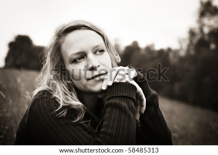 Portrait of young woman sitting in meadow and reflecting on something, sepia toned. - stock photo