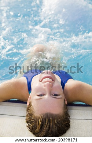 Portrait of young woman sitting in swimming pool, rear view - stock photo
