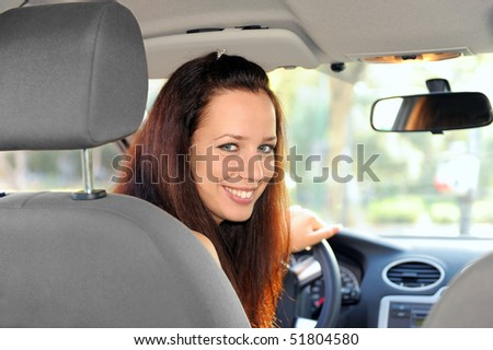 Portrait of young woman sitting in the car, looking back. - stock photo