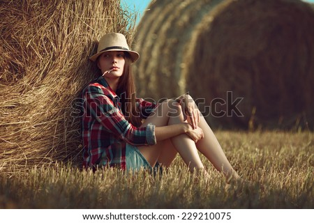 Portrait of young woman sitting next to a stack of hay in sunlight - stock photo
