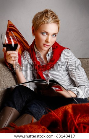 Portrait of young woman sitting on a coach and drinking red wine - stock photo