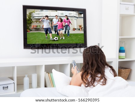 Portrait Of Young Woman Sitting On Couch Watching Television - stock photo