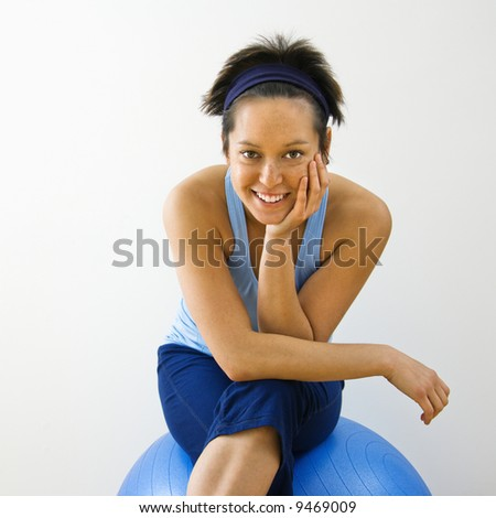 Portrait of young woman sitting on fitness balance ball smiling. - stock photo