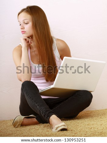 Portrait of young woman sitting on the floor against the wall with a laptop.
