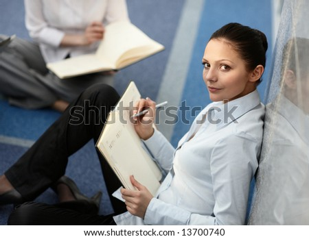 Portrait of young woman sitting with notebook on her lap in modern business office building corridor - stock photo