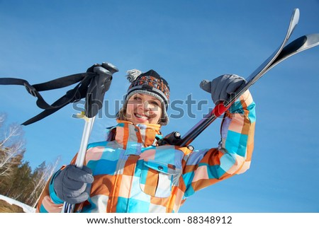 Portrait of young woman skier on blue sky background - stock photo