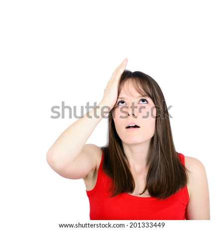 Portrait of young woman slapping hand on head having a duh moment - stock photo