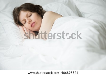 Portrait of young woman sleeping in bed. Female model relaxing in the morning at home under warm blanket - stock photo