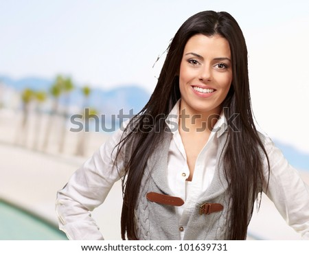 portrait of young woman smiling against a beach