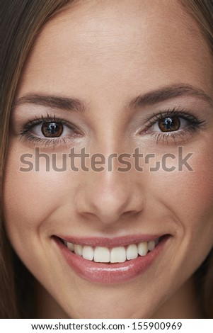 Portrait of young woman smiling, close up