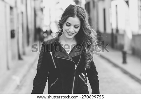 Portrait of young woman smiling in urban background wearing casual clothes with long curly hair - stock photo